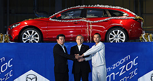 Mazda 2013 Mazda6 First look: Mazda's representative director and chairman of the board, president and CEO, Takashi Yamanouchi is flanked by employees at the unveiling of the new Mazda6 wagon in Japan.